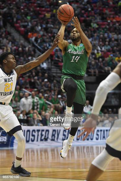 Burks of the Marshall Thundering Herd shoots against Wesley Harris of the West Virginia Mountaineers in the first half during the second round of the...