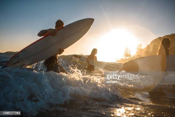 burleigh heads surfers coming out of water at sunrise - coral sea stock pictures, royalty-free photos & images