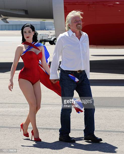 Burlesque artist Dita Von Teese and Founder and President of Virgin Group Sir Richard Branson walk across the tarmac at McCarran International...