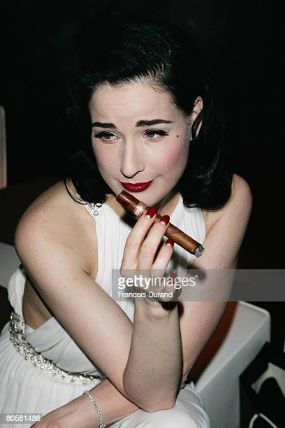 Burlesque artist Dita von Teese smokes a cigar as she attends the 'Writing Time', Robert Wilson's watch launch gala hosted by Montblanc during the...