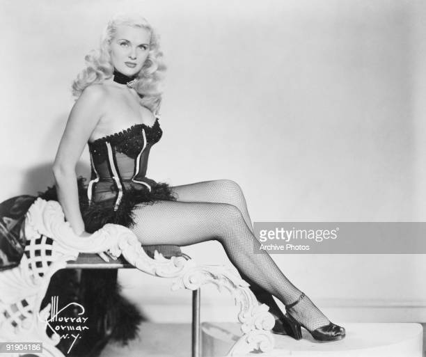 A burlesque dancer in a stage outfit of fishnet stockings basque and choker circa 1955