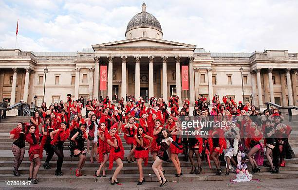 Burlesque dancer Kimberley Dunne poses with a group of Virgin Holidays staff in Trafalgar Square, central London during a photocall to launch the...