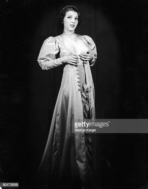 Burlesque dancer Margie Hart baring part of her chest as she performs striptease w her dress fully open in front at 42nd St Apollo Theater