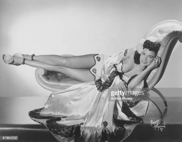 Burlesque dancer Mary Mack reclining on a chaise longue circa 1950