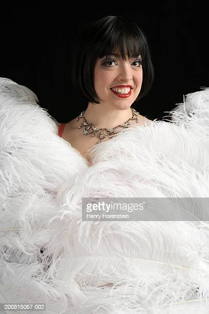 burlesque dancer smiling over ostrich feather fans, portrait - burlesque stock pictures, royalty-free photos & images
