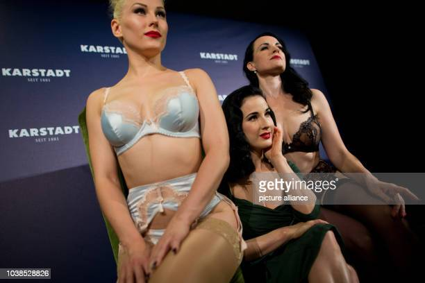 Burlesque model Dita von Teese poses for the camera with two models presenting her new lingerie collection within a newly renovated Karstadt shop in...