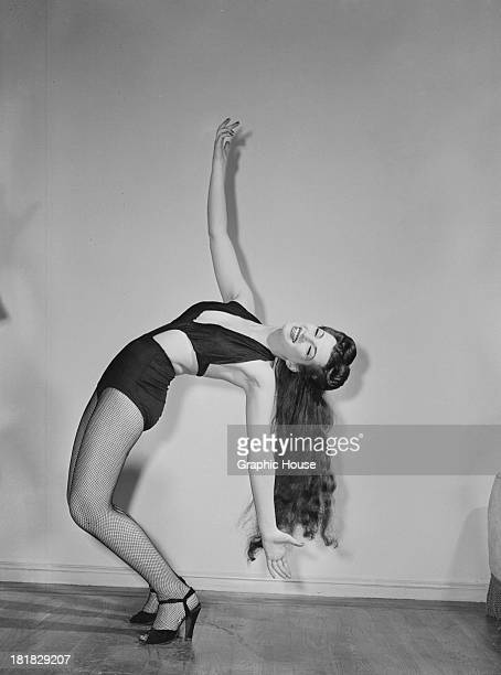 A burlesque performer bending over backwards in a onepiece stage costume and fishnet stockings circa 1945