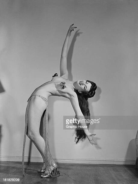 A burlesque performer bending over backwards in a twopiece stage costume circa 1945