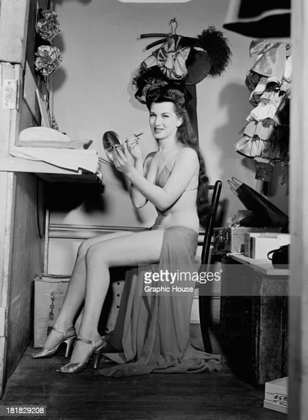A burlesque performer putting on makeup backstage circa 1945