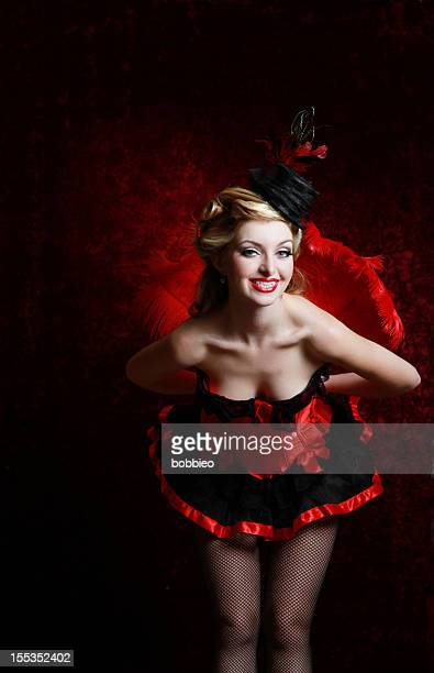 Burlesque woman in red holding feather fan