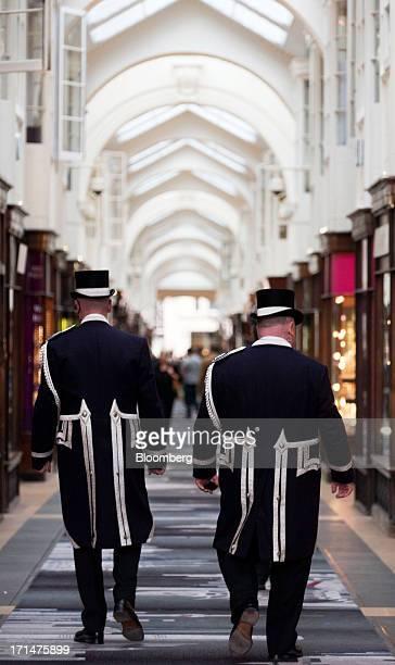 Burlington Arcade Beadles in traditional top hats and frockcoats walk past luxury shops inside Burlington Arcade in London UK on Monday June 24 2013...