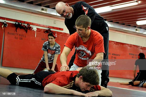Burlington cougars head coach Doug Duell works the kinks on 135 pounder Colin Eberhart as he works on 145 pounder Trenton Rico during their last...
