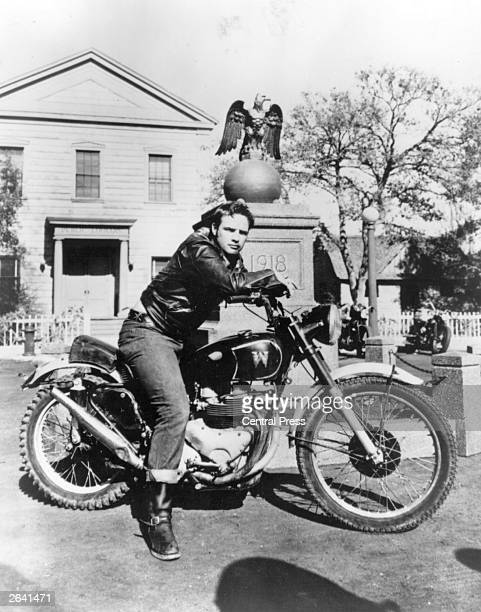 Burly American actor Marlon Brando sitting astride his motorbike in a scene from the classic film 'The Wild One' directed by Laslo Benedek for...