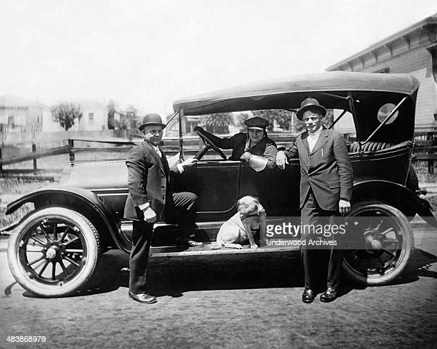 A burly woman wearing a hat and work gloves sits at the wheel while two men and a dog stand nearby mid to late 1910s