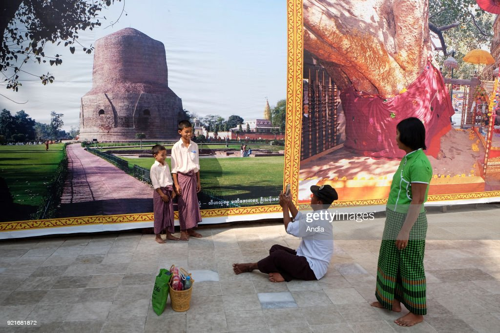 Burmese tourists taking pictures of each other in front of giant posters in Rangoon.