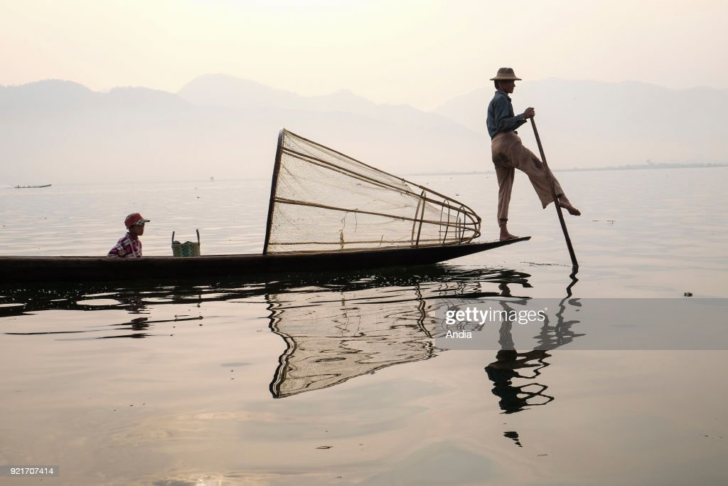 fisherman on a barge on Inle Lake. Fisherman with his son on a barge and cone-shaped fish trap.