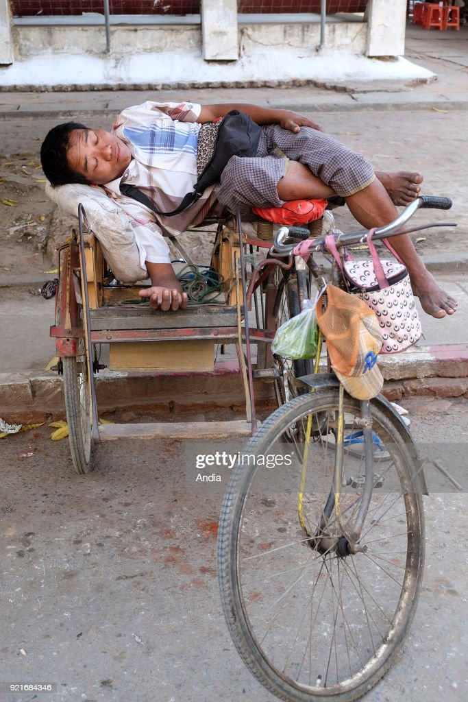 Driver of tricycle, asleep. : News Photo