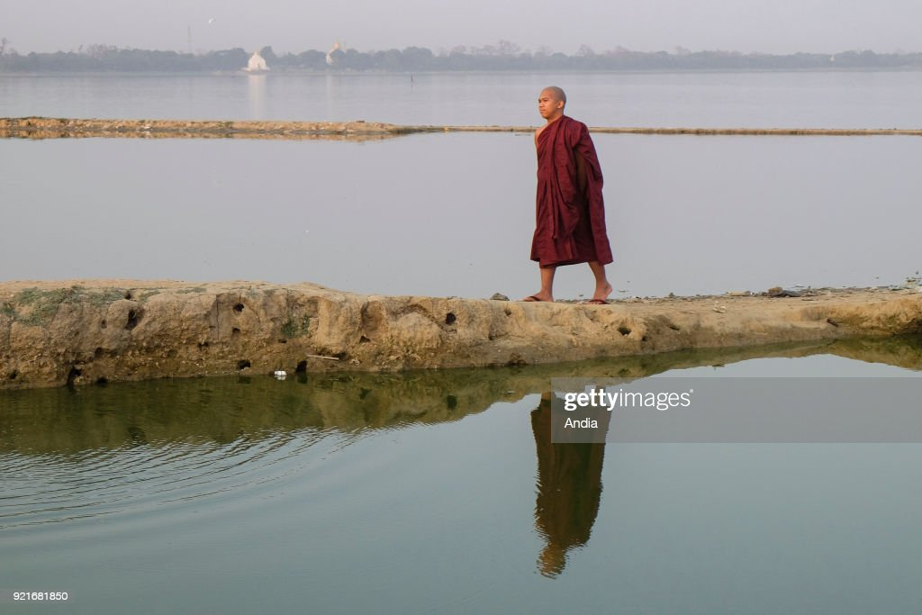monk walking on a path leading to Taungthaman Lake.