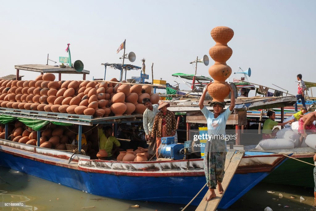 unloading of pieces of pottery on the wharf of the Irrawaddy river. Woman carrying earthenware on her head.