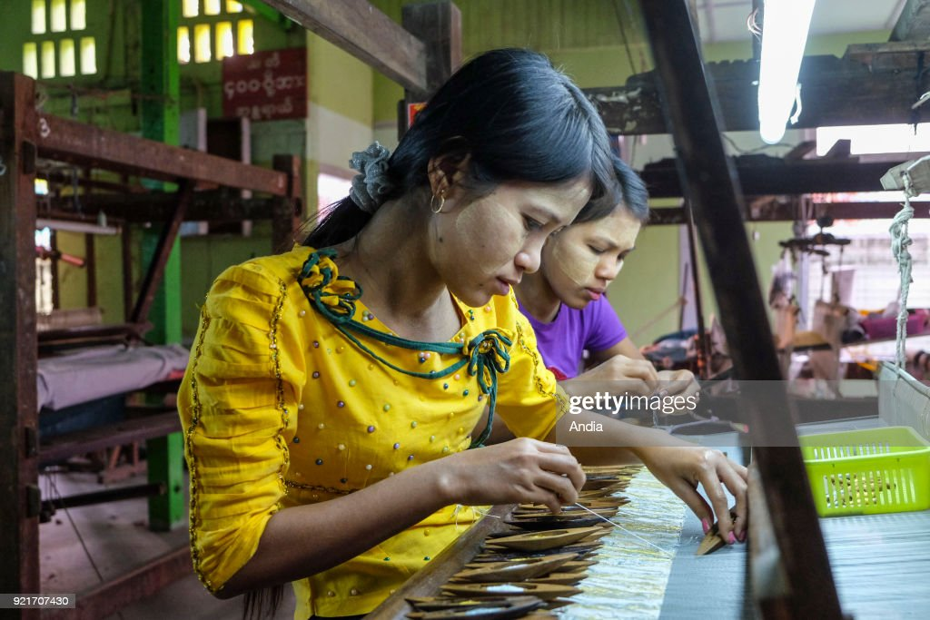 weaving workshop. Women working in front of a weaving loom: young women, weavers with Thanaka, a yellow beauty product, on their cheeks.