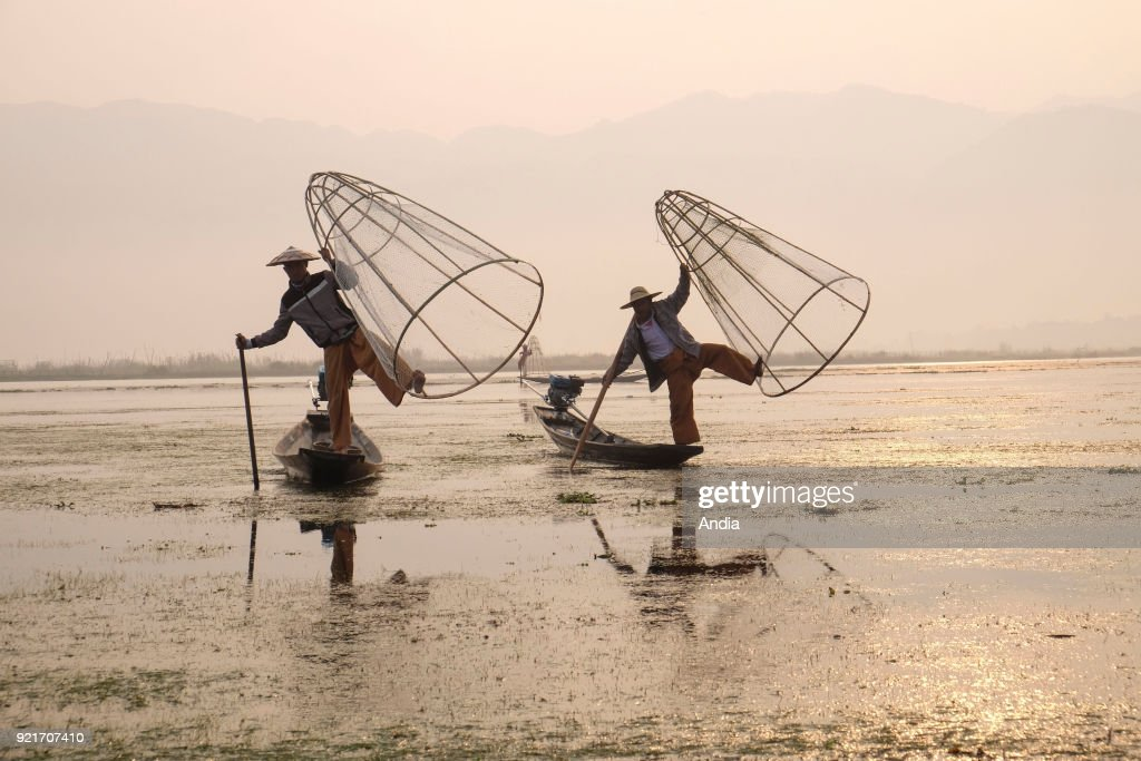two fishermen on barges on Inle Lake. Fishermen and cone-shaped fish trap.