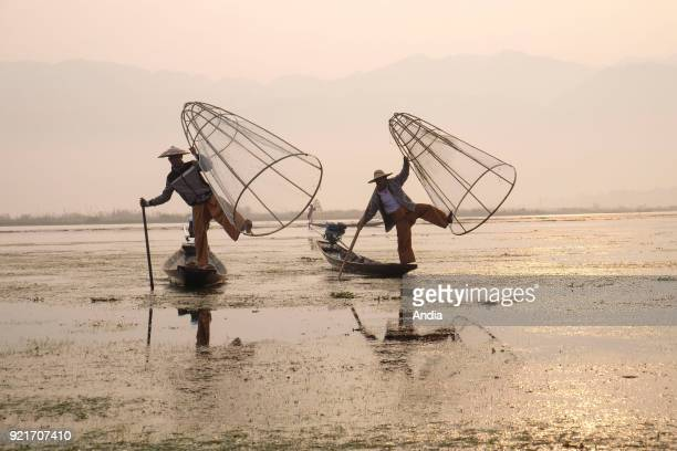 two fishermen on barges on Inle Lake Fishermen and coneshaped fish trap