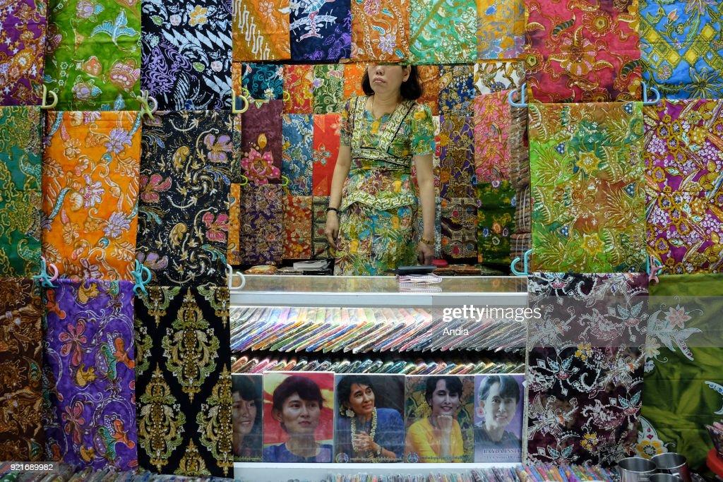 woman selling fabric at Bogyoke Market in Rangoon, and portraits of Aung San Suu Kyi.