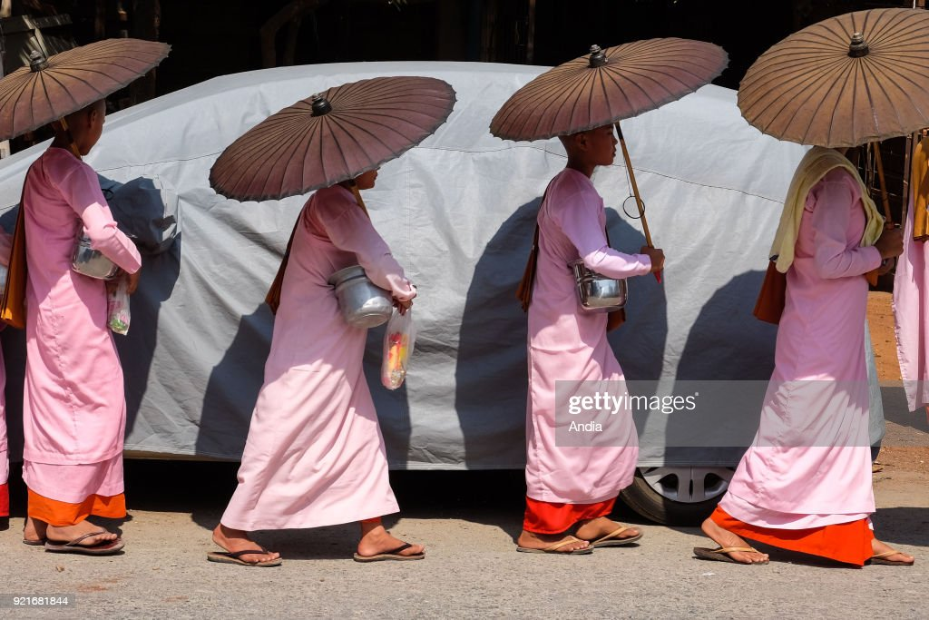 young Buddhist nuns, wearing pink tunics and holding sunshades, begging in a street of Mandalay.
