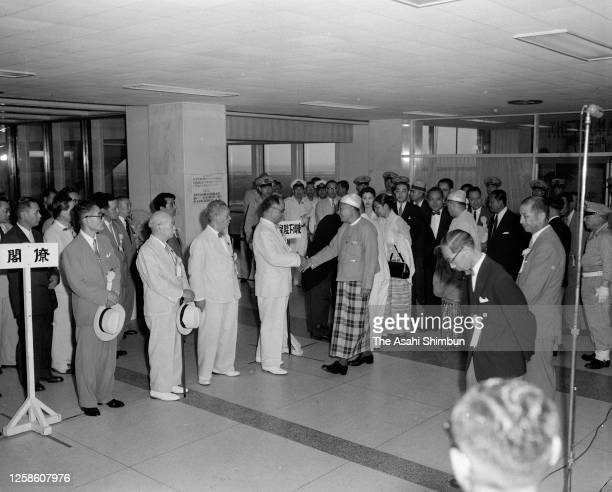 Burma Prime Minister U Nu shakes hands with Japanese Foreign Minister Mamoru Shigemitsu on arrival at Haneda Airport on July 19, 1955 in Tokyo, Japan.
