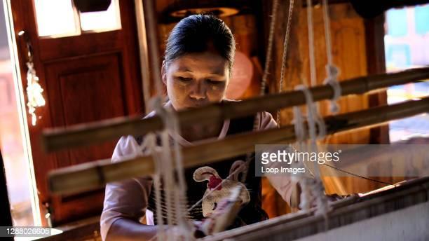 Burmese artisan weaver works a loom making silk at the floating village at Inle Lake.