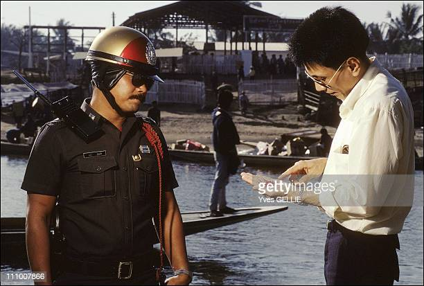 Burmese border In Mae Sot two police officers examina a small pack of rubies coming from Burma on the other side of the river