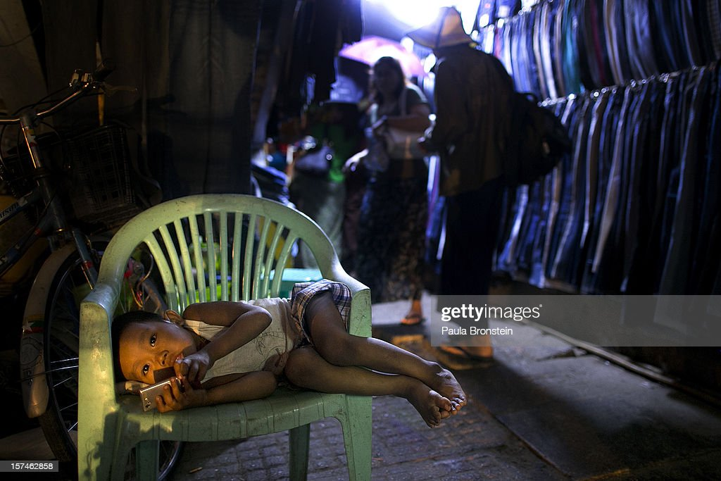 A Burmese boy plays with a mobile phone waiting for his father to finish work November 30, 2012 in Yangon, Myanmar. Business is booming in this newly opened Southeast Asian country. Import restrictions have been eased resulting in many new cars seen on the streets.