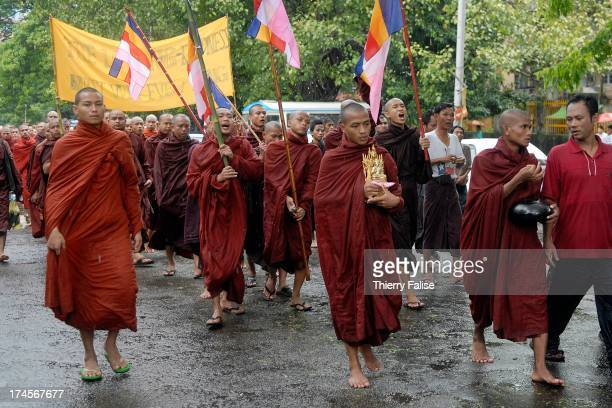 Burmese Buddhist monks protesting against the military junta are marching in the streets of Rangoon. At the front of the column, a monk carries an...