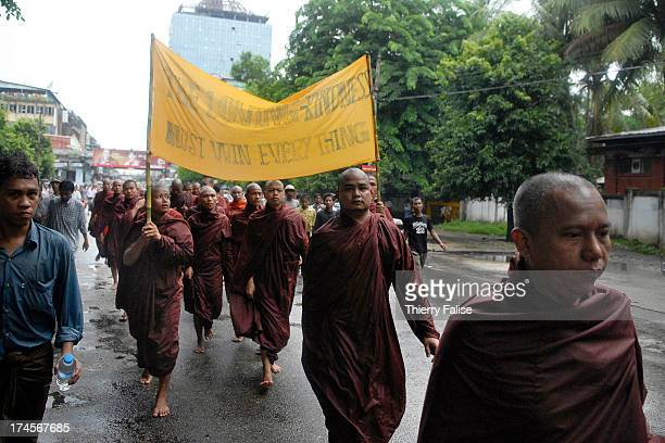 Burmese Buddhist monks protesting against the military junta are marching in the streets of Rangoon. At the front of the column, two monks brandish a...