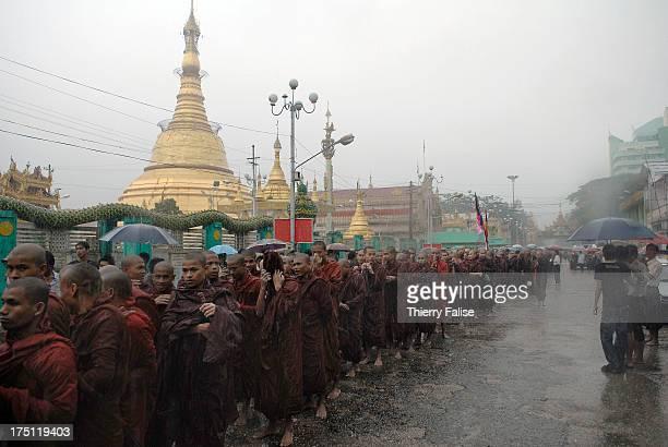 Burmese Buddhist monks protesting against the military junta are marching under heavy monsoon rain past the Botahthaung pagoda in Rangoon
