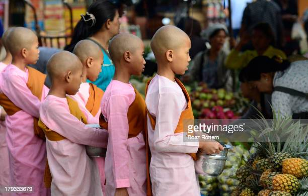 CONTENT] Burmese Buddhist nuns collecting food offerings at the central market in Kengtung Eastern Shan state Myanmar