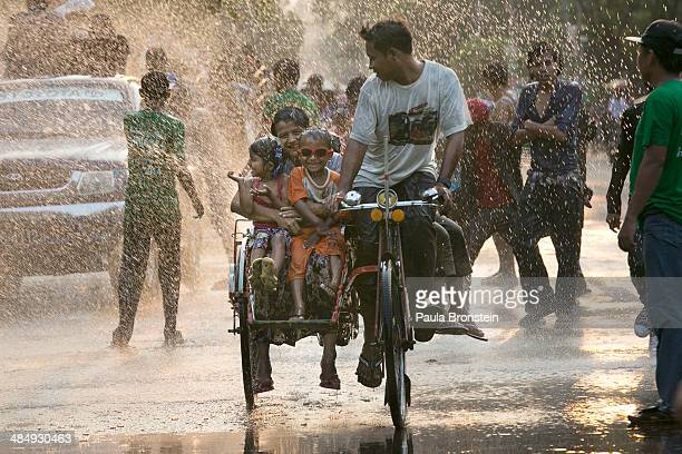 Burmese celebrate as they are sprayed with water during the third day of the Burmese new year water festival called Thingyan in Yangon Myanmar April...