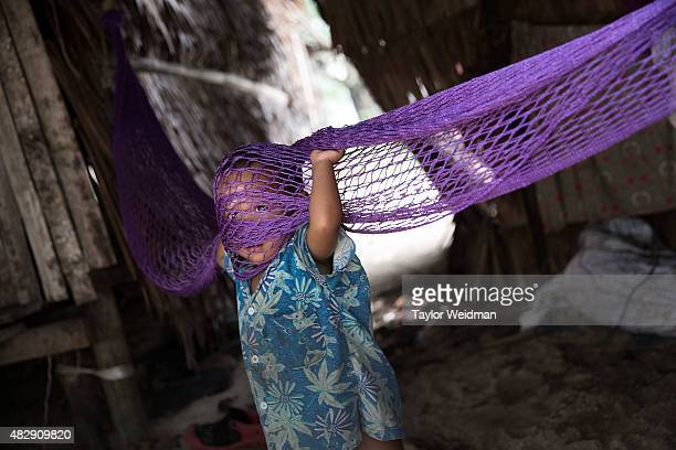 Burmese child plays in a hammock in a village inside the planned Dawei SEZ on August 3 2015 in Ngapitat MyanmarThe controversial multibillion dollar...