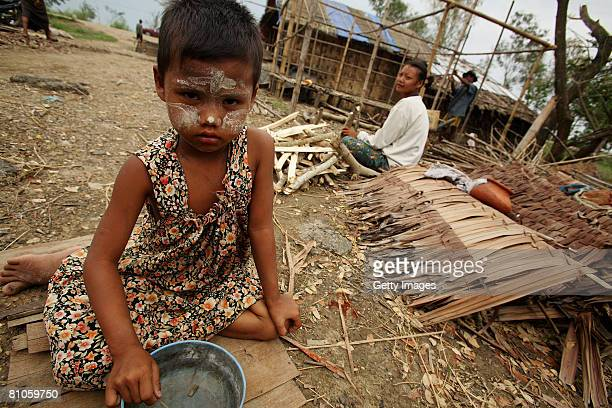 Burmese child sits with an empty bowl as her family rebuild a house on May 12 in Maubin Myanmar It has been estimated that more than 100000 people...