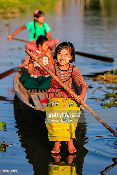 Burmese children row a boat on Inle Lake