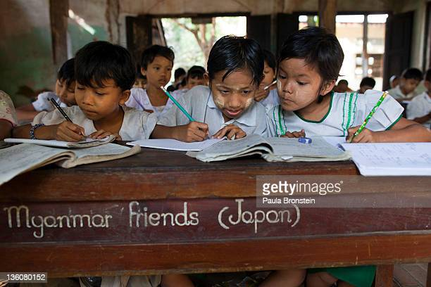 Burmese children share school books during class at a school run by a monastery for impoverished children December 15 2011 in Bago Myanmar The...