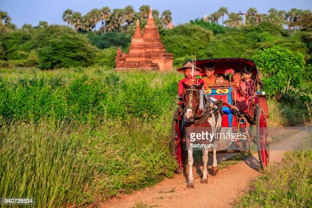 burmese children sitting on a horse cart, bagan, myanmar - myanmar stock pictures, royalty-free photos & images