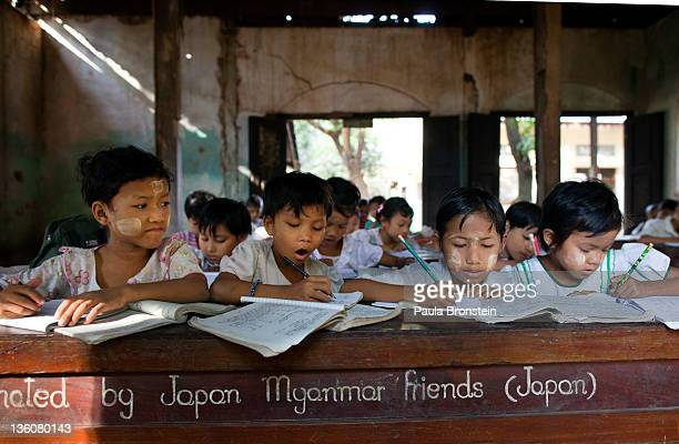 Burmese children work at a school run by a monastery for impoverished children December 15 2011 in Bago Myanmar The education system is based on the...