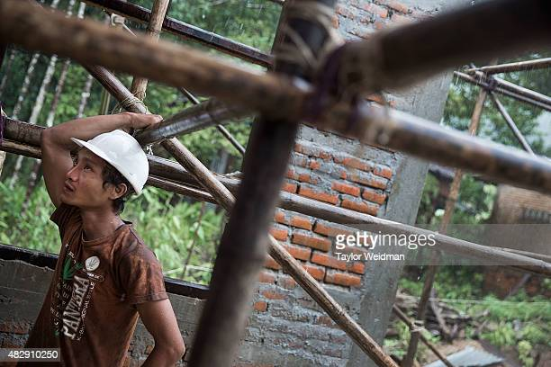 Burmese construction workers build an elementary school near the planned Dawei SEZ on August 4 2015 in Maungmagan MyanmarThe controversial...