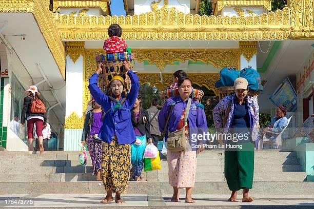 Burmese female porter carrying heavy bags and kids insede their bamboo back basket in Kyaiktiyo Pagoda, Myanmar on Mar 10, 2013