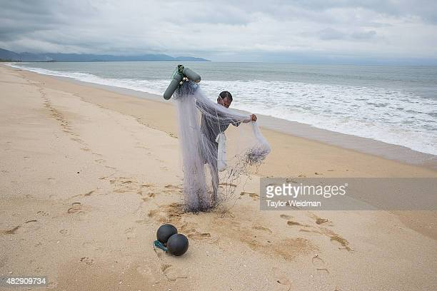 Burmese fisherman collects his nets after fishing on the beach where the Dawei deep sea port is planned to be built on August 3 2015 in Nabule...