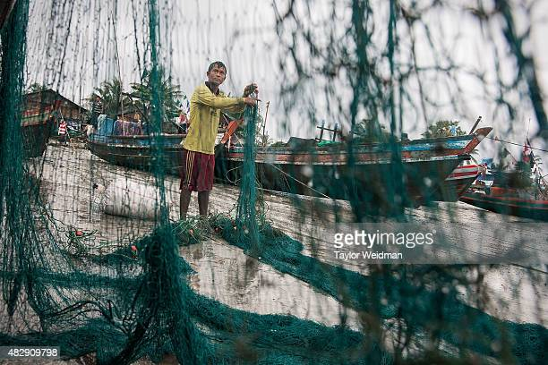 Burmese fisherman works near a boat in his village near the planned Dawei SEZ on August 2 2015 in Bawar Village Myanmar The controversial...