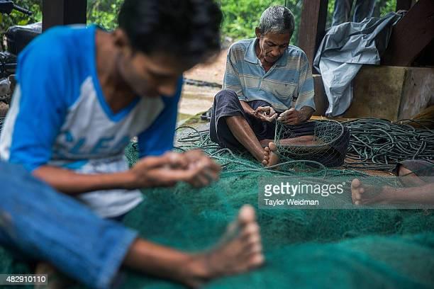 Burmese fishermen mend nets in their village near the planned Dawei SEZ on August 4 2015 in Pantininn Myanmar The controversial multibillion dollar...
