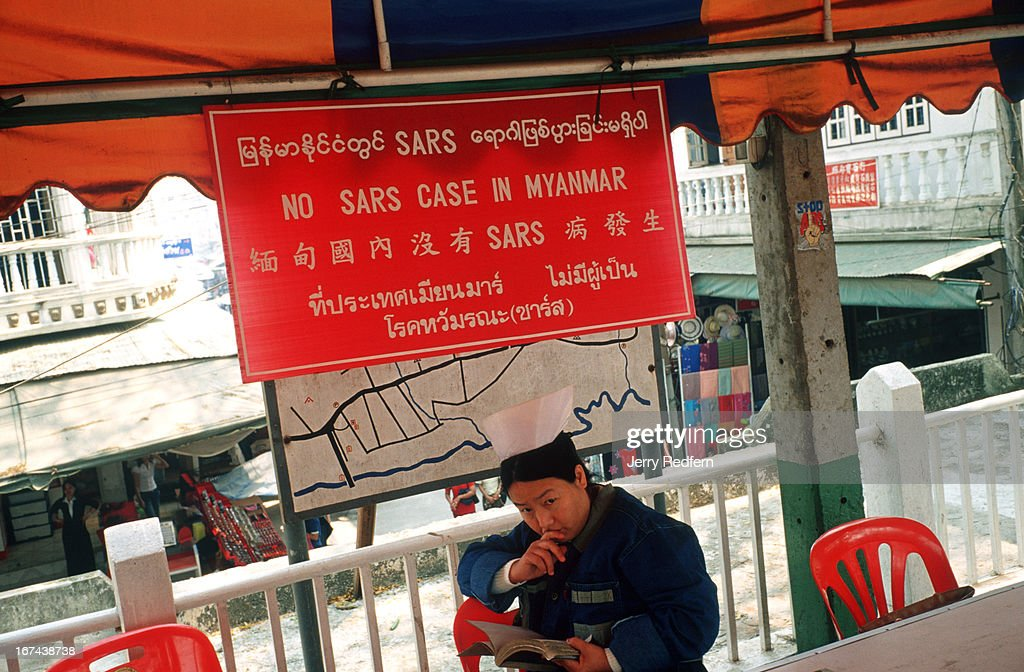 A Burmese government medical examiner reads a book while ostensibly watching for people infected with the SARS virus at the border crossing with the Thai town of Mae Sai..