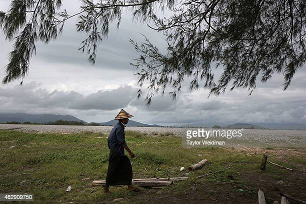 Burmese man walks back to his motorbike after hunting with a slingshot inside the planned Dawei SEZ on August 3 2015 in Nabule Myanmar The...